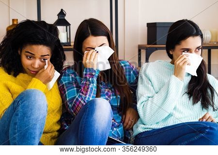 Multiracial Girls In Casual Wear Sitting On Sofa In Living Room, Watching Sad Movie And Crying, Home