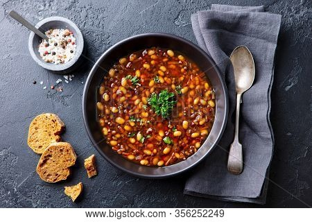 Bean Soup In A Black Bowl. Dark Background. Top View.
