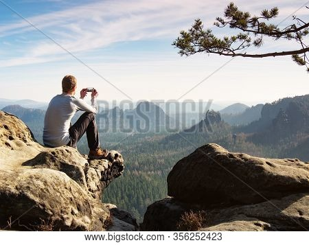 Influencer Takes And Share Phone Photos While Sit On The Edge. Risky Job For Young Travel People.