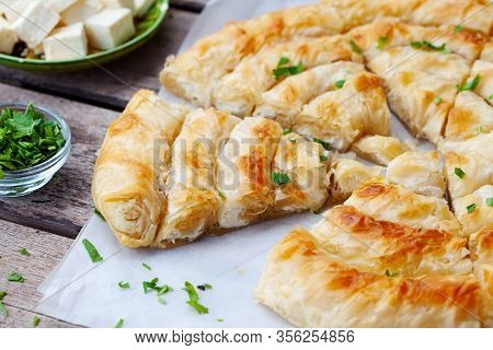 Traditional Feta Cheese Phyllo Pastry Pie, Banitsa. Wooden Background. Close Up.