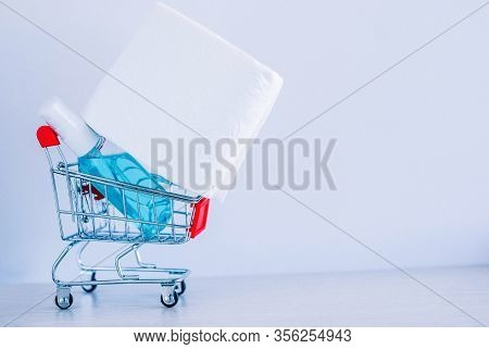 A Roll Of White Toilet Paper And Sanitizer In A Shopping Cart As A Symbol Of Consumer Panic About Co
