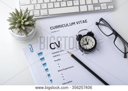 Curriculum Vitae With Clock On Work Desk