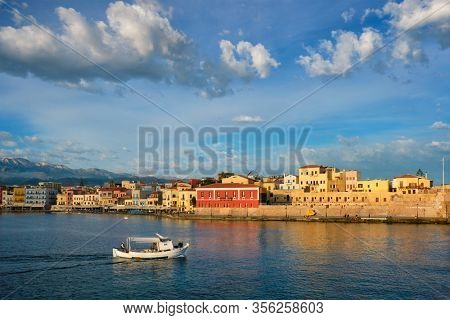 Fishing boat going to sea in picturesque old port of Chania is one of landmarks and tourist destinations of Crete island in the morning. Chania, Crete, Greece