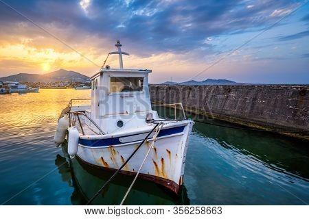 Old fishing boat in port of Naousa on sunset with dramatic sky. Paros lsland, Greece