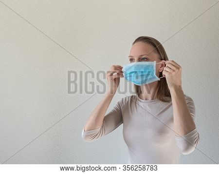 A Woman Putting On A Medical Disposable Mask To Avoid Contagious Viruses.