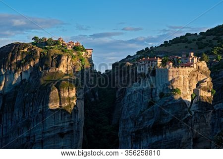 Monastery of Varlaam and Great Meteoron Monastery in famous greek tourist destination Meteora in Greece on sunrise. Horizontal camera pan