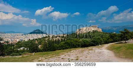 Panorama of famous greek tourist landmark - the iconic Parthenon Temple at the Acropolis of Athens as seen from Philopappos Hill, Athens, Greece