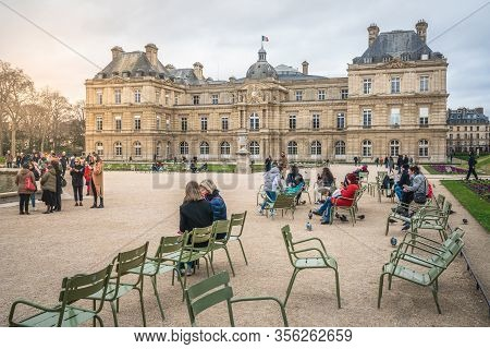 Paris France, 23 February 2020 : People Resting On Iconic Green Chairs At Jardin Du Luxembourg Garde