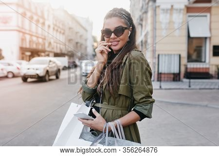 Smiling Brunette Lady In Dark Sunglasses Walking Around Town And Listening Music. Outdoor Portrait O