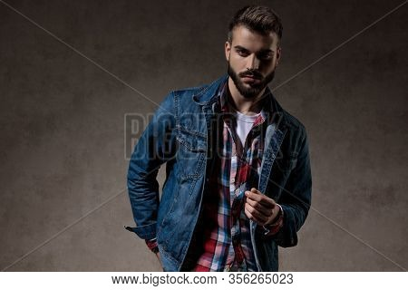 Tough model holding his hand behind his back while wearing jeans jacket and standing on wallpaper studio background