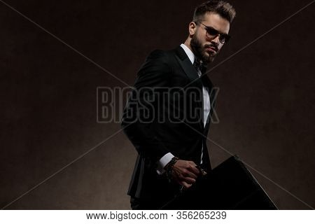 Bothered fashion businessman holding briefcase while wearing suit and sunglasses, walking on a wallpaper studio background