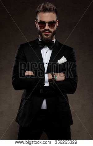 Tough fashion groom holding his hands crossed while wearing suit and sunglasses, standing on a wallpaper studio background