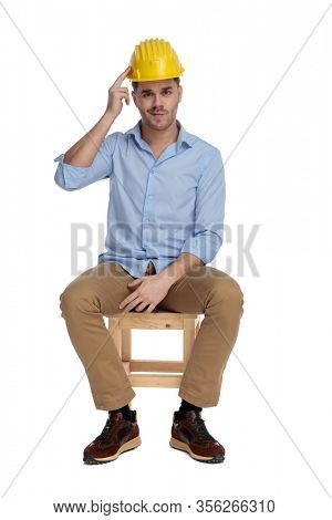 Bothered casual man pointing at his hard hat and frowning while sitting on a chair on white studio background