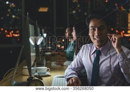 Portrait Of Asian Male Customer Care Service With Businesswoman Smiling And Working Hard Late In Nig