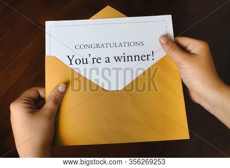 An Open Shiny Gold Envelope With A Letter That Says Congratulations You're A Winner! With Female Han