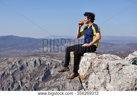Young Man Resting On A Cliff With A Gorgeous View. Concept Of Freedom. Man Eating On A Cliff Edge