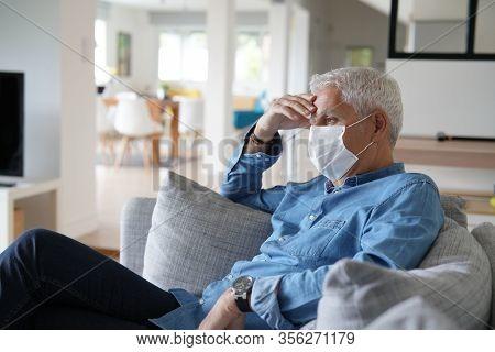 Senior man being sick and wearing protection mask, coronavirus