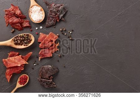 Jerky. Set of various kind of dried spiced meat, diverse peppercorns and salt on wooden spoons  on dark gray background. Top view with copy space. Snack for beer.
