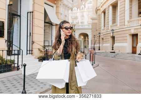Serious Brunette Fashionista Lady Talking On Phone During Shopping In Autumn Weekend. Good-looking S