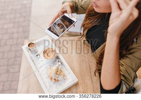 Close-up Portrait Of Tanned Female Model Making Photo Of Her Dessert In Outdoor Cafe. Overhead View