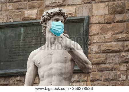 The Statue Of David in the Piazza della Signoria In Italy Wearing Blue Protective Medical Face Mask.
