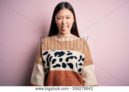 Young beautiful asian woman wearing animal print fashion sweater over pink isolated background sticking tongue out happy with funny expression. Emotion concept.