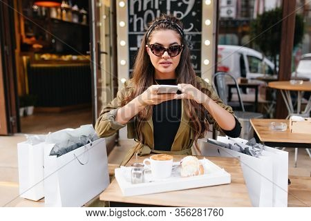 Pretty Girl In Dark Sunglasses Sitting In Outdoor Cafe Beside Bags From Boutique. Portrait Of Brown-