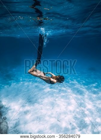 Woman Freediver Glides With Fins Over Sandy Sea Bottom. Freediving And Sun Light In Blue Ocean