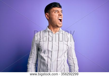 Young handsome hispanic man wearing elegant business shirt standing over purple background angry and mad screaming frustrated and furious, shouting with anger. Rage and aggressive concept.