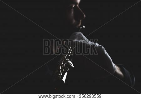 Flutist In A Black Shirt, Against A Dark Background .. Male Executor On A Wooden Wind Instrument