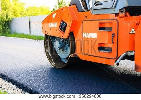 Workers And Asphalting Machines. Heavy Road Roller In Motion On The Roadway. Construction Of A New R
