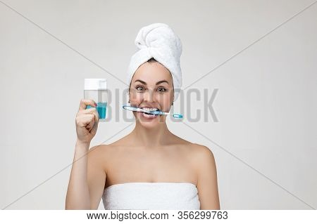 Happy Young Woman In Towel Brush Her Teeth In The Morning. Girl Holding Toothbrush And Mouthwash Gel