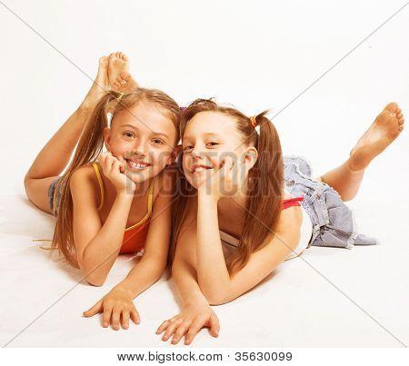 Two beautiful girls  laying on white
