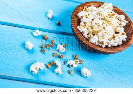 Popcorn In Wood Dish Or Bowl On Blue Table
