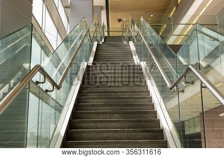 Marble Staircase With Metal Railing In A Shopping Center Or Hospital. Glass Railing. Upwards. Perspe