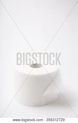 A single roll of white bathroom  toilet paper with a flipped edge on a white dreamlike background, vertical portrait orientation with high-key lighting.