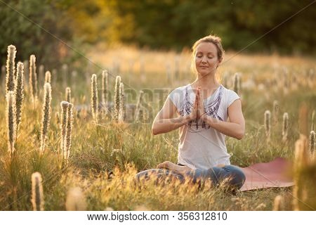 Beautiful Girl Doing Yoga Asanas In Nature At Sunset. Outdoor Fitness And The Concept Of Life Balanc