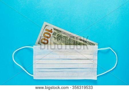 Medical Mask Lie On Banknote Of 100 Dollars On Blue Background. Concept Of Deficit, Speculation And