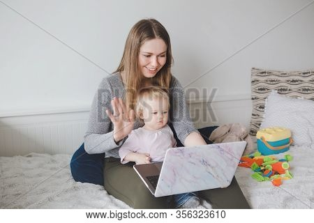Young Caucasian Mother Blogger With Baby Working On Laptop From Home. Workplace Of Freelance Woman S