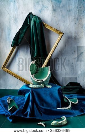 Stilllife With Remnants Of Broken Teal Colored Vase, Emerald Green And Dark Blue Velvet, And Picture
