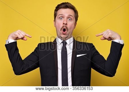 Positive Young Man With Mustache Smiling And Pointing At Himself With Index Fingers. Handsome