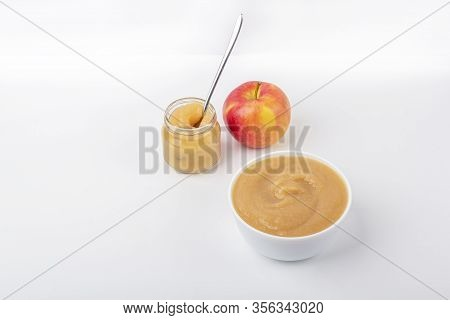 Fresh Homemade Applesauce In White Bowl And Jar With Fruit Puree On White Table. The Concept Of Prop