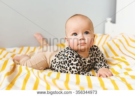 Happy Baby With Cute Smile Sitting In A Cot. Child Sitting In The Bed. Happy Childhood.