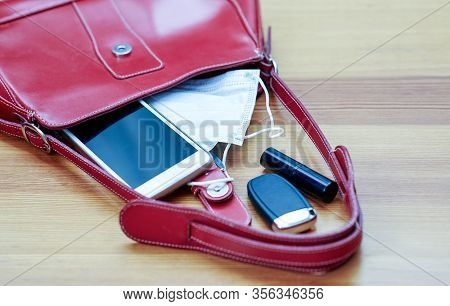 Red Woman Bag With Protruding Two Sanitary Masks, Mobile Phone, Lipstick And Keys. Antivirus Concept