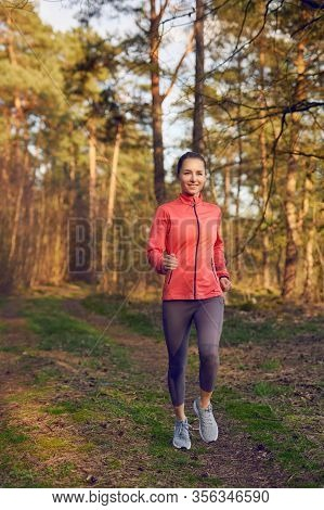 Healthy Fit Attractive Young Woman Jogging In Woodland Along A Forest Track Approaching The Camera W