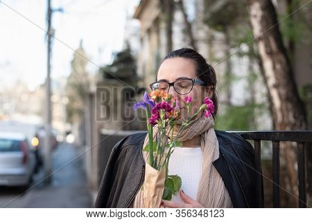 Beautiful Woman Smelling Flowers On Street. Happy People Lifestyle. Woman Smelling Flowers In Sunshi