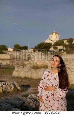 A Religious Pregnant Young Woman Thinks About Her Baby And Strokes Her Belly On The Roof Of A Christ