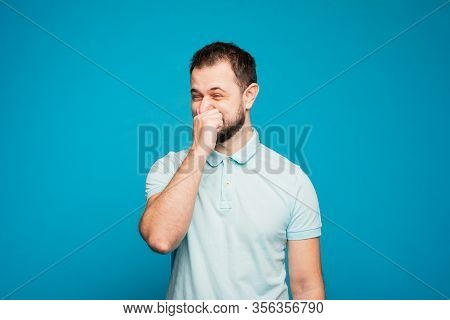 A Man In A Blue T-shirt On A Blue Background Funny Sneezes In His Hand. You Can Not Sneeze In The Ha