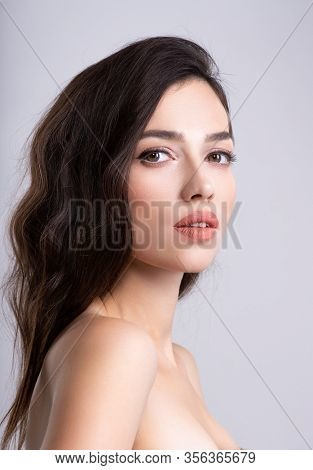 Woman with beauty brown hair. Portrait of brunette woman with beautiful  hairstyle. Fashion model, at studio. Beautiful young woman with long brown hair.  Clean fresh clean skin face.