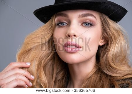 Fashion model in black jacket and black hat. Beautiful face of an attractive model with blue eyes.  Blonde long brown hair and natural makeup.  Stylish fashion model. Woman dressed in black. Art.